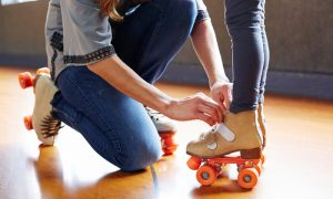 mother tying roller skates on child